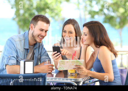 Group of tourists checking smart phone and map on vacation in a coffee shop or hotel on the beach - Stock Image