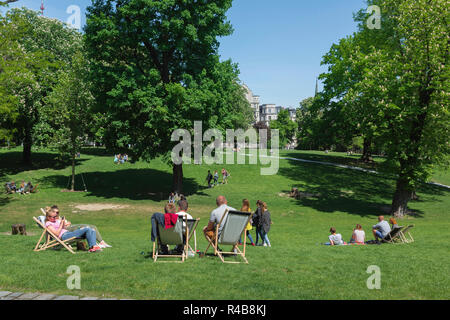 Park summer, rear view of young people relaxing in deckchairs on a summer afternoon in Dabrowskiego Park in Poznan, Poland. - Stock Image