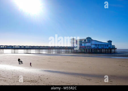 Weston Super Mare, UK. 20th February, 2018. A young mother makes the most of some rare winter sunshine, and blue - Stock Image