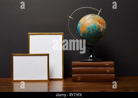 globe on books near blank frames on table - Stock Image