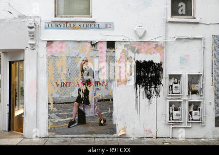Tattered poster featuring Vinti Andrews model defaced and torn with graffiti on a the wall at Turville Street Shoreditch East London E1  KATHY DEWITT - Stock Image