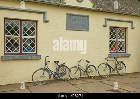 Three bicycles leant against a white washed building wall. - Stock Image