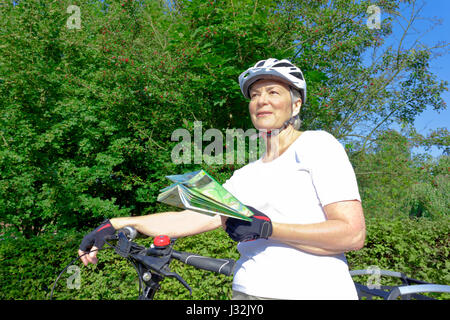 Senior woman outdoors in the summer sun with bicycle helmet, gloves, white t-shirt and map, looking for the right - Stock Image
