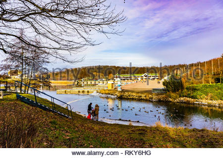 Poznan, Poland - February 10, 2019: Adults and children feeding ducks by a lake on a cloudy winter day. Buildings and a forest in the background. The  - Stock Image