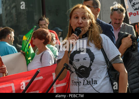 London, UK. 13th August 2018.  A woman in a 'Free Lula' t-shirt introduces a speaker at the Brazilian protest outside the Brazilian embassy calling for the release of Luiz Inacio Lula da Silva, a former trade union leader who was President of Brazil from 2003-11 to enable him to stand for election again in October. Credit: Peter Marshall/Alamy Live News - Stock Image