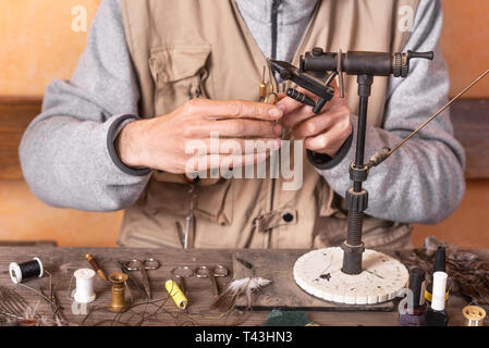 Man making trout flies. Fly tying equipment and material for fly fishing preparation . - Stock Image