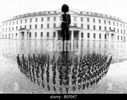 A guard and tiny toy soldiers. - Stock Image