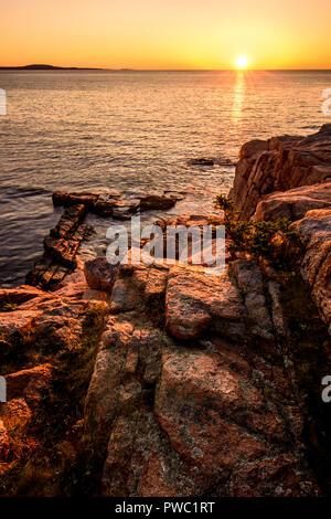 Sunrise over the rocky shoreline of Acadia National Park, Maine. - Stock Image