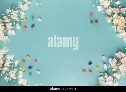 Jelly beans and spring flowers over a teal / blue background with room for copy space. Image shot from top view. - Stock Image