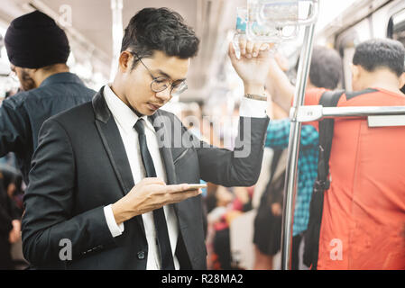 young and handsome asian businessman using smarphone in a commuter train. concept of business people and wireless technology - Stock Image