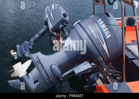 Two Yamaha four stroke outboard motors out of the water attached to the back of a boat - Stock Image