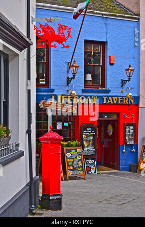 The colourful exterior of the Lifeboat Tavern in Tenby with vintage red Post Box & traditional red dragon sign hanging from wall.Tenby, S.Wales - Stock Image