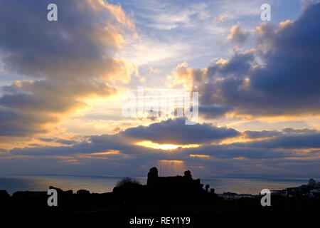 The sun sets over Hastings Castle, East Sussex, UK - Stock Image