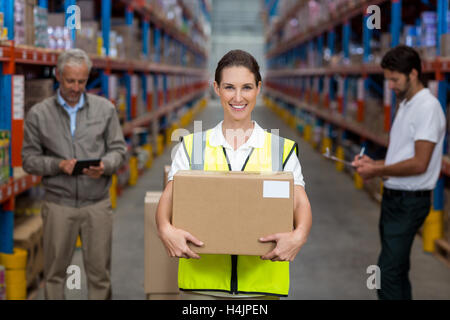 Female worker holding cardboxes while colleague working in background - Stock Image