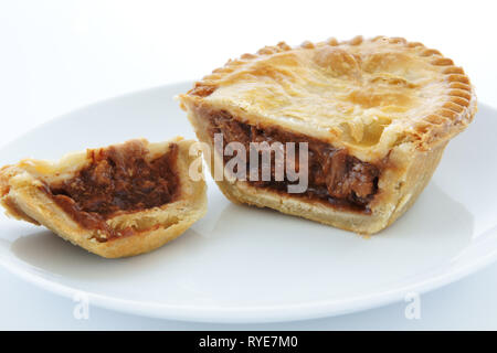 Savoury meat pie with a beef filling on a white plate - Stock Image