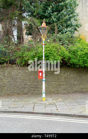 Painted decorative lamp post with bright red post box attached - Stock Image