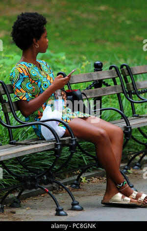 NEW YORK, NY - JULY 10: Young black woman on a bench on a hot summer day in Washington Square Park in Manhattan on JULY 10th, 2017 in New York, USA. - Stock Image