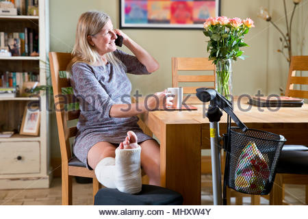 Mature Woman With Leg In Plaster Cast Sitting By Table At Home Talking On Phone - Stock Image