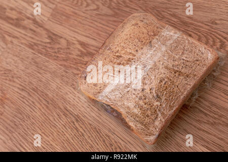 Prepared packed lunch consisting of sandwich wrapped in clingfilm on wooden table background - Stock Image