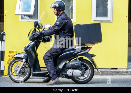 London England United Kingdom Great Britain Lambeth South Bank Southbank Centre center food delivery service motorcycle motor scooter man delivery hel - Stock Image