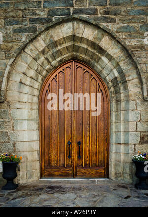A large wooden oak arched doorway on St. Peter's Roman Catholic Church, Brownsville, Pennsylvania, USA - Stock Image