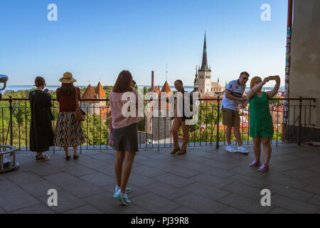 Tourism tourists Europe, view of tourists on Toompea Hill taking photos of themselves and the medieval Old Town quarter of Tallinn, Estonia, Europe. - Stock Image