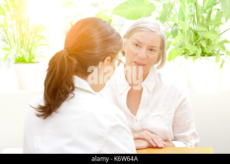 Senior patient discussing something in confidence with her female doctor of geriatrics on a sunny afternoon, friendly atmosphere - Stock Image