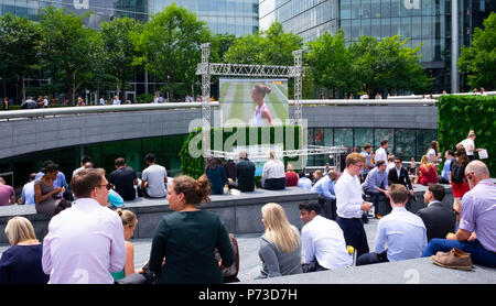 London, England. 4th July 2018. Tourists and office workers watch the tennis at Wimbledon on a giant screen on another very hot day. The present heatwave is set to continue. ©Tim Ring/Alamy Live News - Stock Image