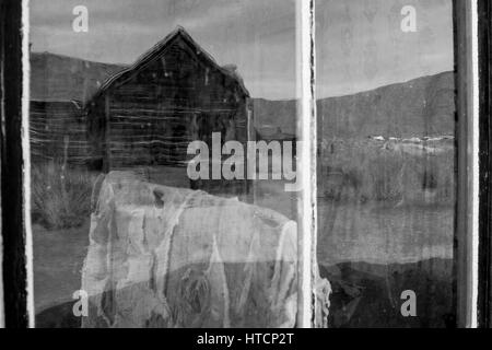 A reflection in the window in Bodie. The Bodie State Park is the remains of Bodie, a silver and copper mining town - Stock Image