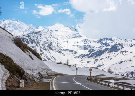 Looking south down the E62 from the summit of the Simplon Pass towards Italy with snow covered alpine peak. - Stock Image