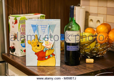 Le Carillon red french wine in a bottle next to a Winnie the Poo present bag on a wooden kitchen table - Stock Image