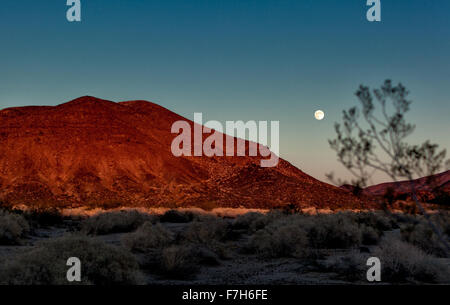 Moon rise over a lava cone in Mojave - Stock Image