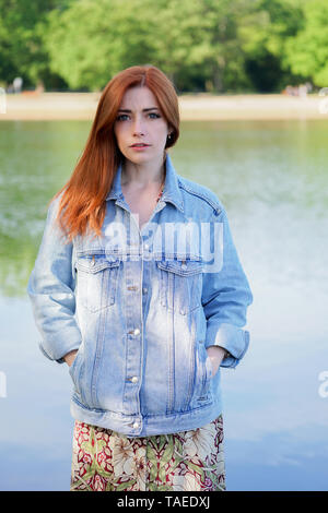 young woman wearing denim jacket over summer dress standing by lake - authentic real people - Stock Image