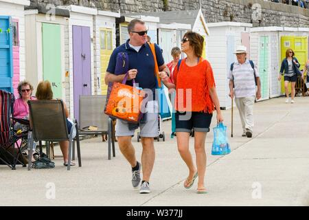 Lyme Regis, Dorset, UK.  13th July 2019. UK Weather.  A couple enjoying a walk along the seafront at the seaside resort of Lyme Regis in Dorset on a warm cloudy day.  Picture Credit: Graham Hunt/Alamy Live News - Stock Image
