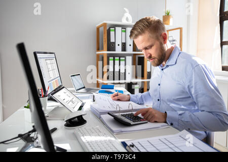 Businessperson Calculating Invoice With Computer On Desk - Stock Image