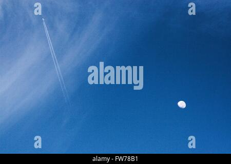 Waxing/waning moon against blue sky with clouds and jet trails. - Stock Image
