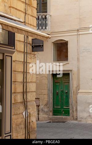 A narrow street and doorway in Valletta, Malta - Stock Image