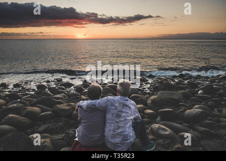 Senior couple viewed from back hug and love enjoying the sunset at the berach during summer vacation lifestyle - concept of relationship and life toge - Stock Image