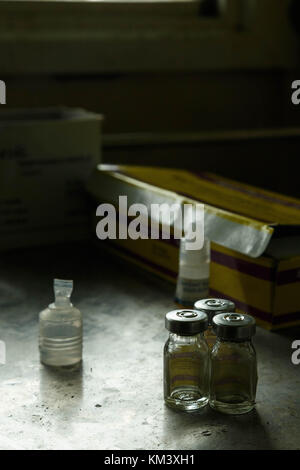 Used injection bottles lie in a pile in a village clinic in Papua New Guinea - Stock Image