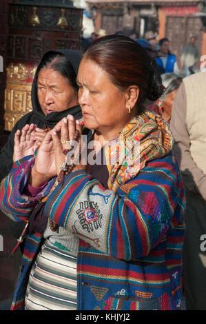 Female pilgrims in prayer at the Boudhanath (Bodhnath) Stupa outside Kathmandu, Nepal - Stock Image