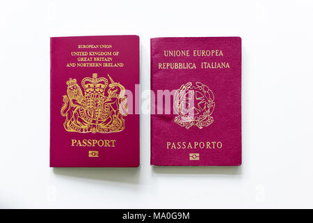 British and Italian passports next to each other on white desk. - Stock Image
