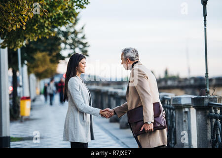 Mature man and young woman business partners standing outdoors in city of Prague, shaking hands. - Stock Image