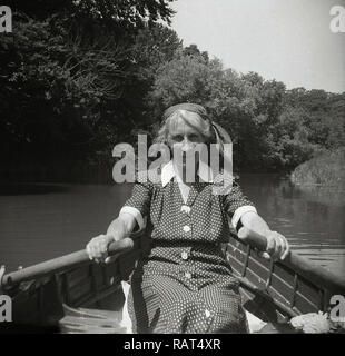 1950s, historical, a middle-aged lady in a spotted dress oars in hand sitting in a rowing boat rowing down a river on a summer's day, England, UK. - Stock Image