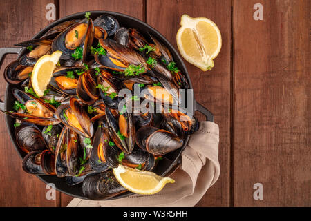 Marinara mussels, moules mariniere, with lemon slices, in a cooking pot, shot from the top on a dark rustic wooden background with copy space - Stock Image
