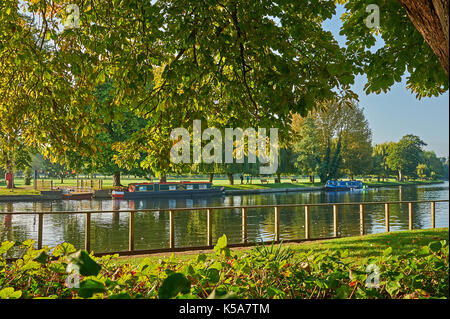 Stratford upon Avon an early morning autumn reflections on the River Avon, with narrow boats moored near the old chain ferry crossing point. - Stock Image