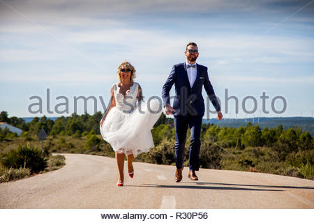 Couple of newlyweds run along the asphalt of a lonely road - Stock Image