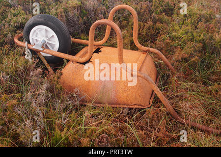 An image of an upturned rusty worn out wheelbarrow laying in wild heather and grass - Stock Image