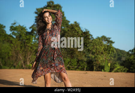 Portrait of a pretty, delicate brunette posing against tropical woods - Stock Image