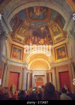 Crowd taking photographs of frescoes inside the Vatican Museum. - Stock Image
