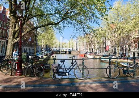 Amsterdam, Netherlands - April 2019: Bikes parked on a canal bridge. - Stock Image